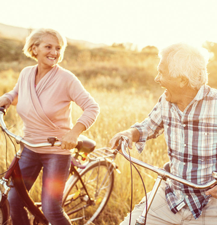 Retired couple riding bikes on their acreage